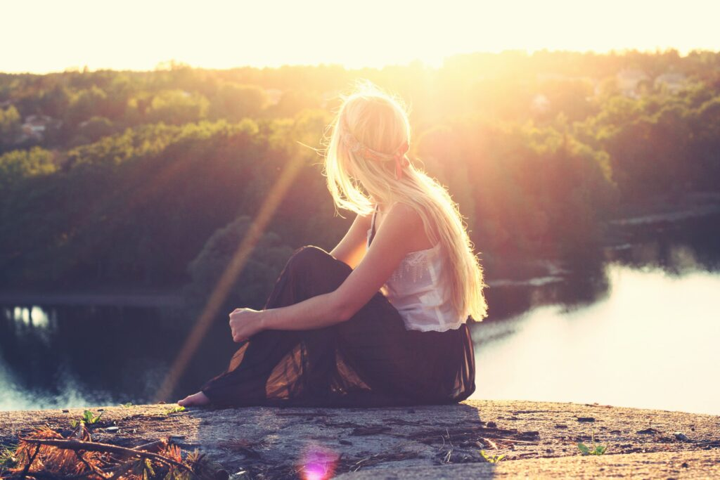 a woman sits on the ground and watches the sun set